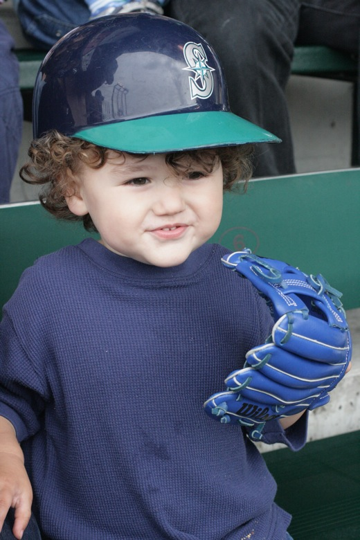 boy with seattle mariners batting helmet and baseball glove
