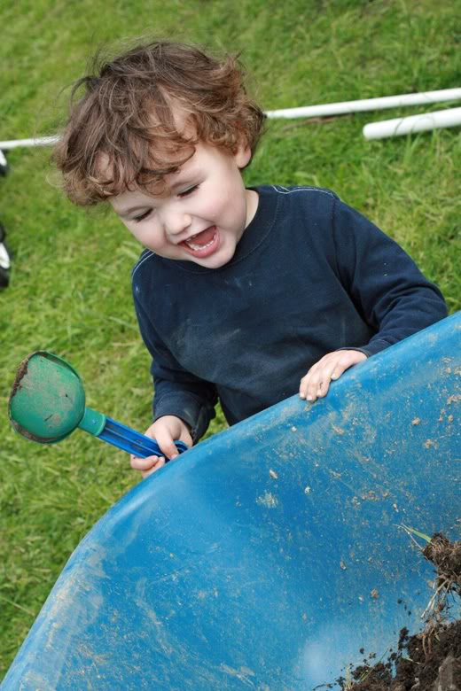 making raised garden beds - boy smiling with shovel