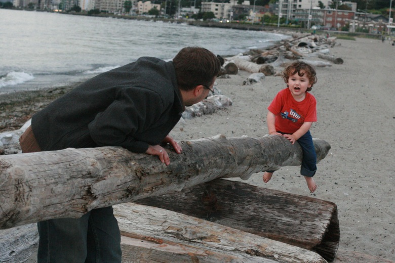 Boy on driftwood seesaw on the beach with father