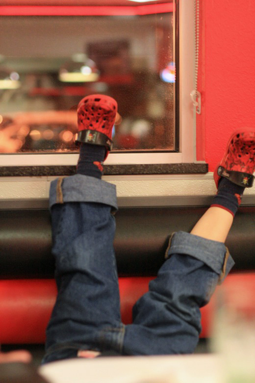 Upside-down legs in a Steak 'n Shake booth