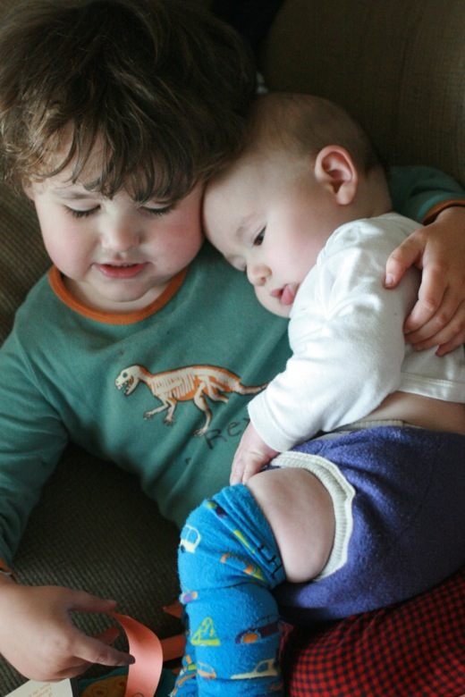brothers snuggling — preschooler with baby on lap
