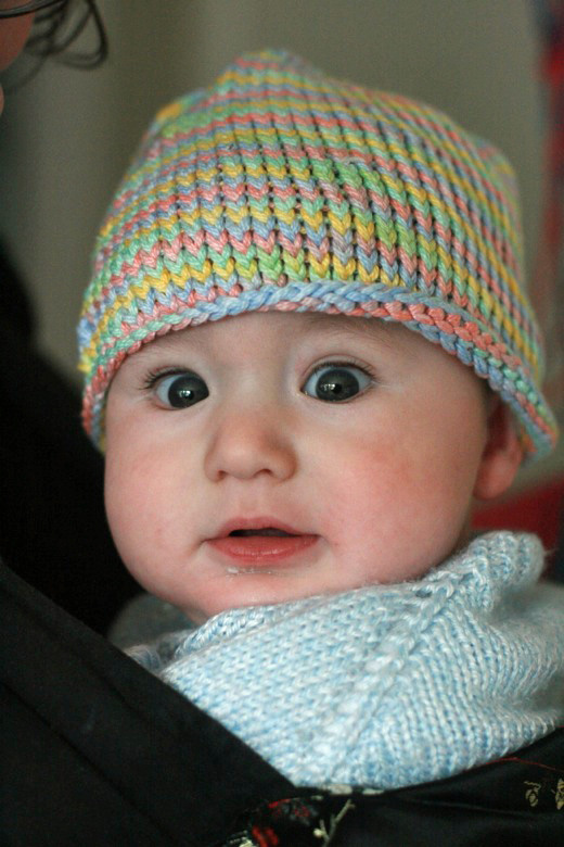 baby bundled up for the cold outside with wide dark blue eyes