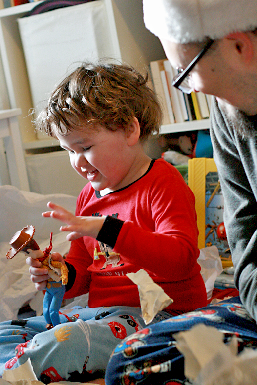 boy opening Woody and presents happily on Christmas morning