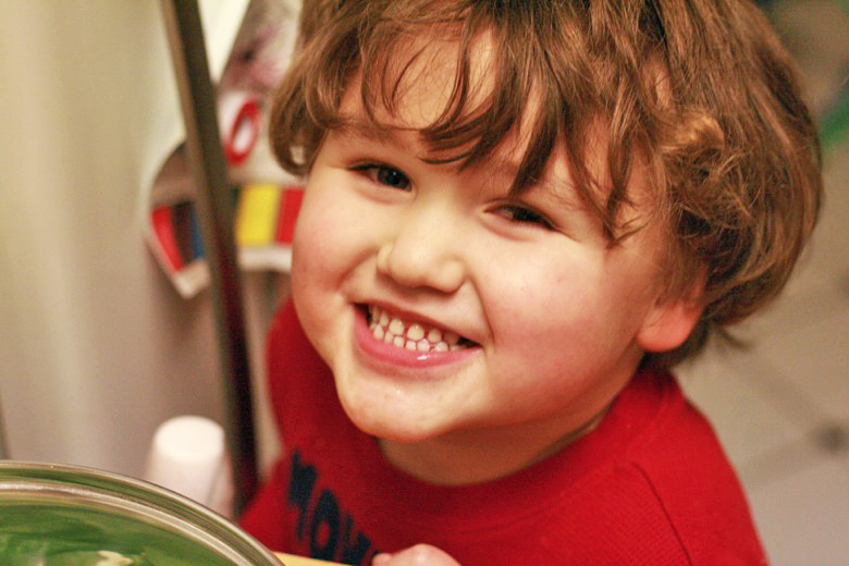 boy smiling in kitchen while cooking