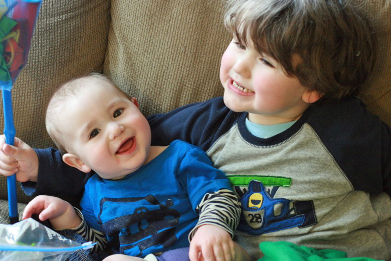 brothers sitting next to each other on the couch — siblings smiling — baby Alrik a8mo mikko m4yo