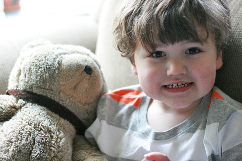 boy smiling next to teddy bear