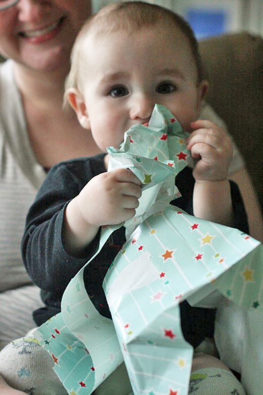 baby eating wrapping paper at birthday