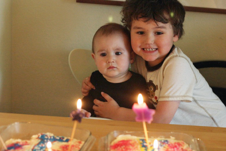 boy and baby with first birthday cake and lit candles