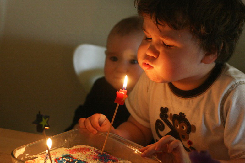 boy blowing out baby's first birthday cake candle