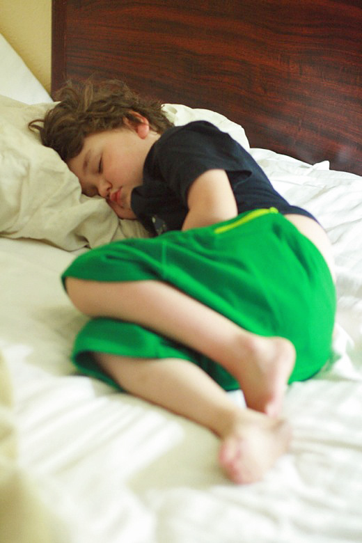 boy sleeping on hotel bed — california road trip travel mikko m5yo