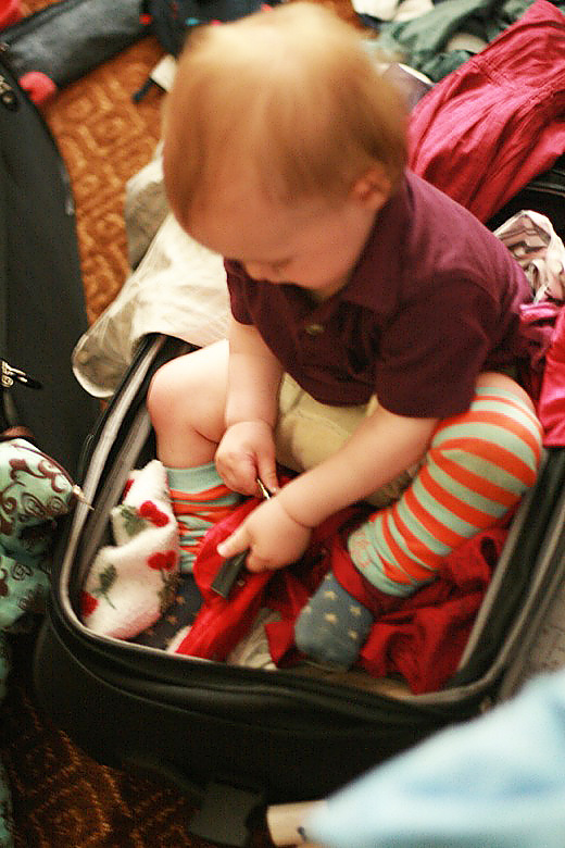 toddler boy sitting in suitcase unpacking
