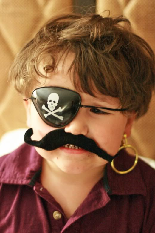 Boy in pirate costume mustache eyepatch and earring