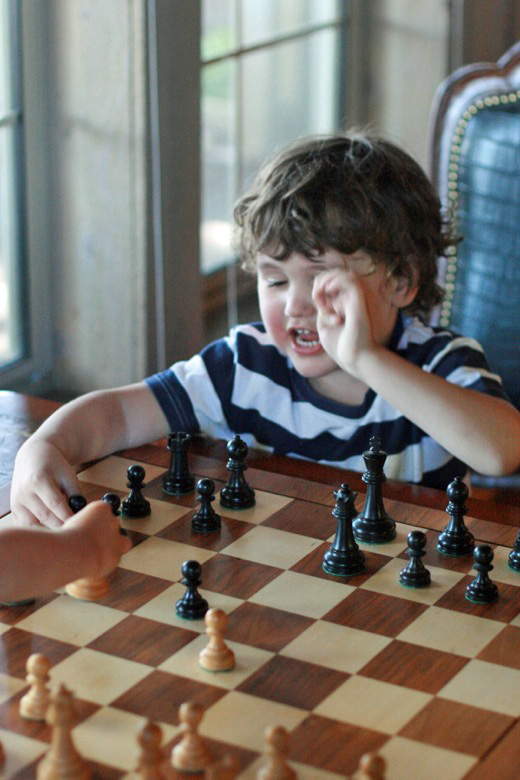 boy playing chess with cousin