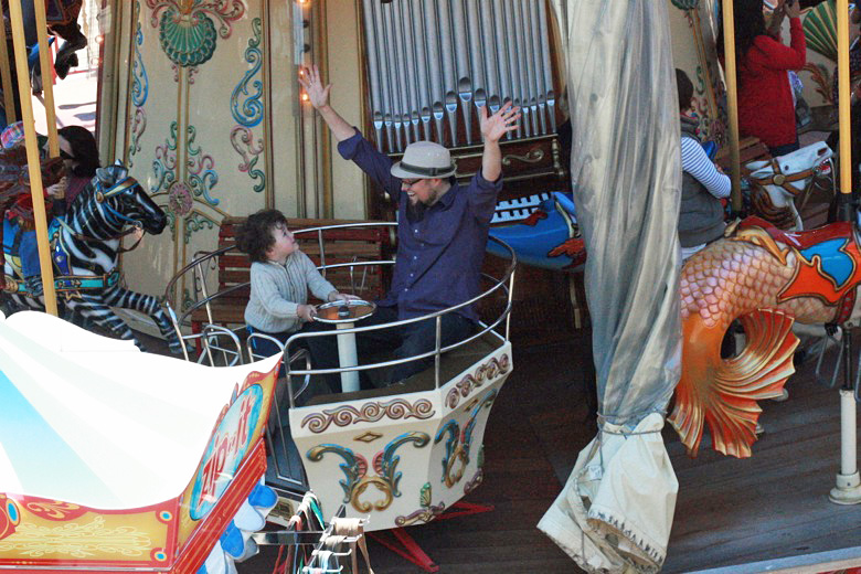 boy and dad enjoying the spinning 2-story carousel — california road trip travel san francisco
