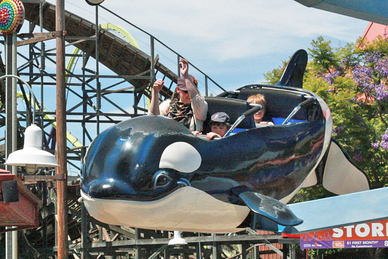 mom and son on amusement park orca ride — Six Flags California