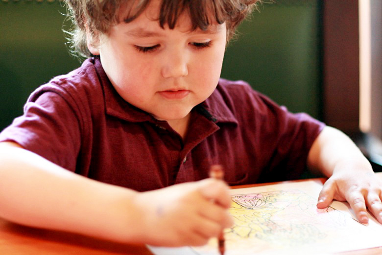 boy coloring at restaurant table