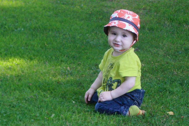 toddler boy sitting on grass