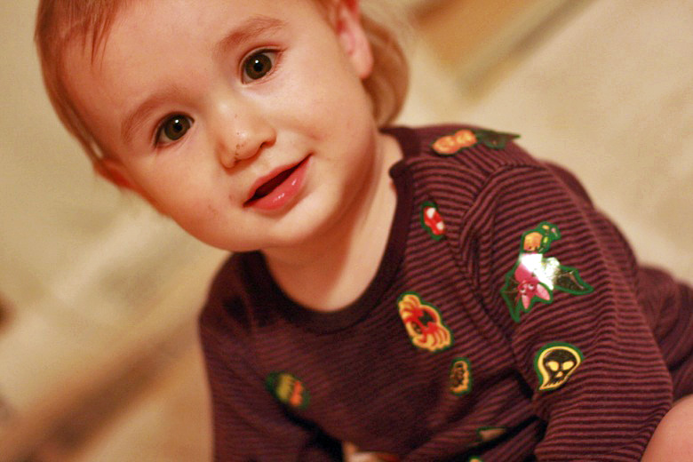 toddler boy with stickers all over his shirt