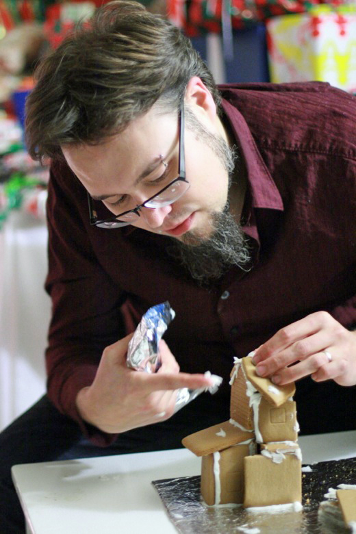 dad constructing gingerbread house — holidays Christmas12