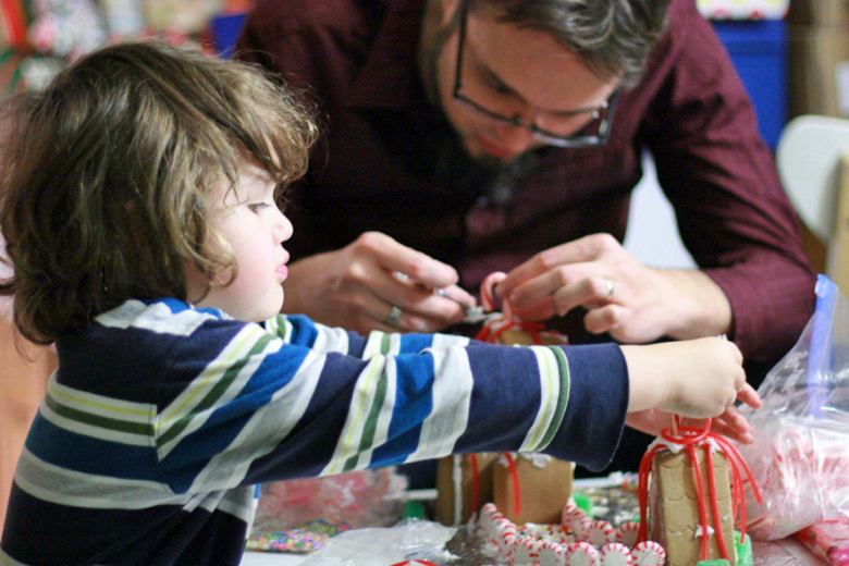 boy and dad decorating gingerbread house — holidays Christmas12