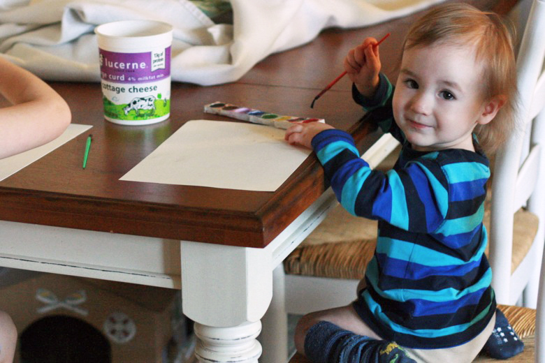 toddler painting with watercolors at table - crafts art