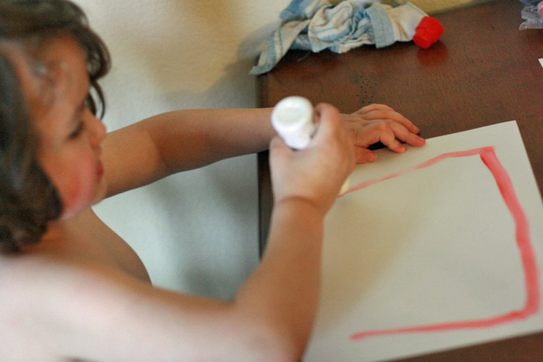 boy painting with dot paint sticks at table - crafts art