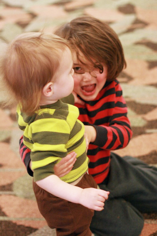 two happy boys attacking each other at the mall - brothers siblings