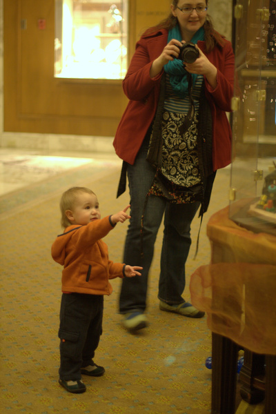 baby pointing at gingerbread house display case — Christmas downtown Seattle meetup holidays