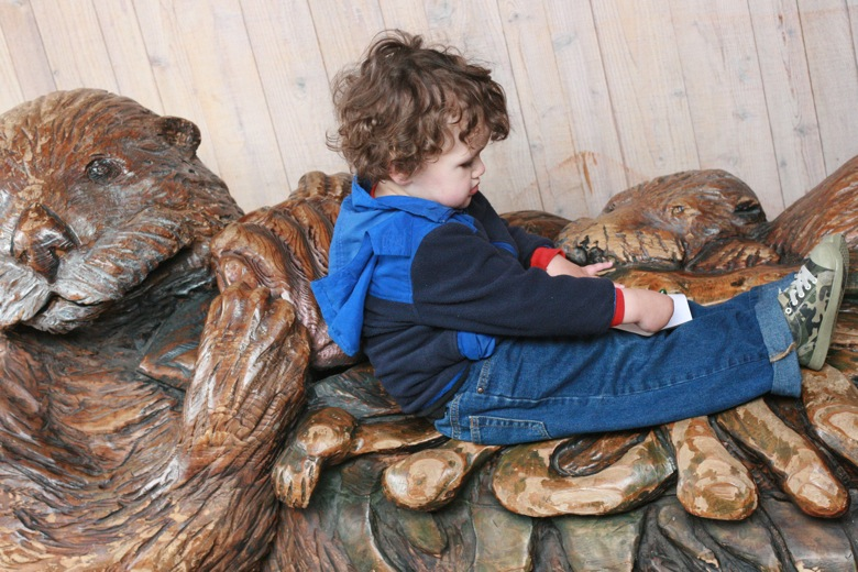 boy sits on sea otter sculpture bench Seattle Aquarium