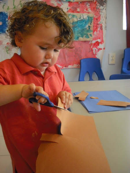 toddler cutting construction paper artwork with scissors