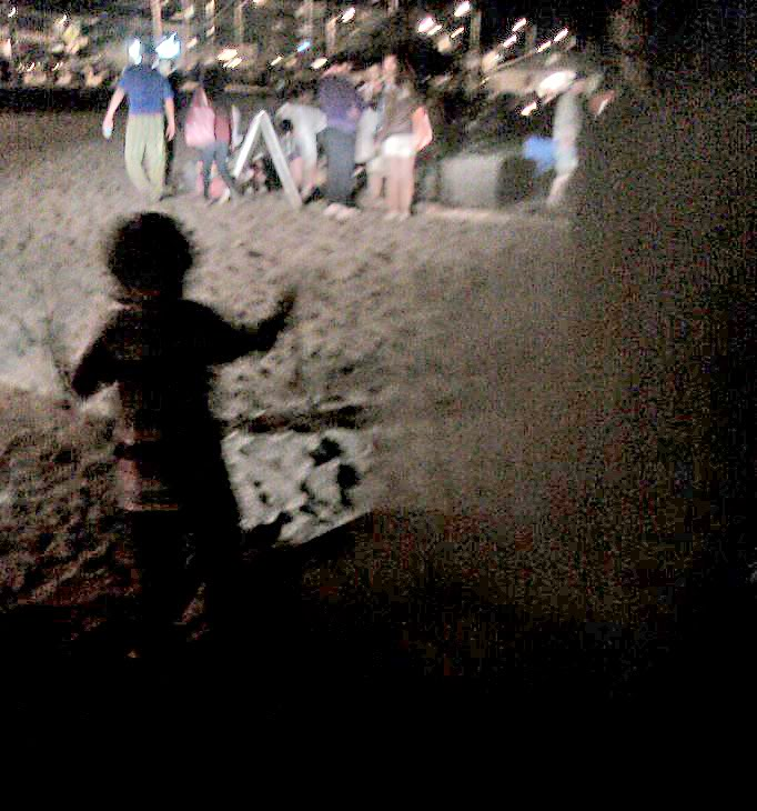 boy frolicking near fire pits on beach