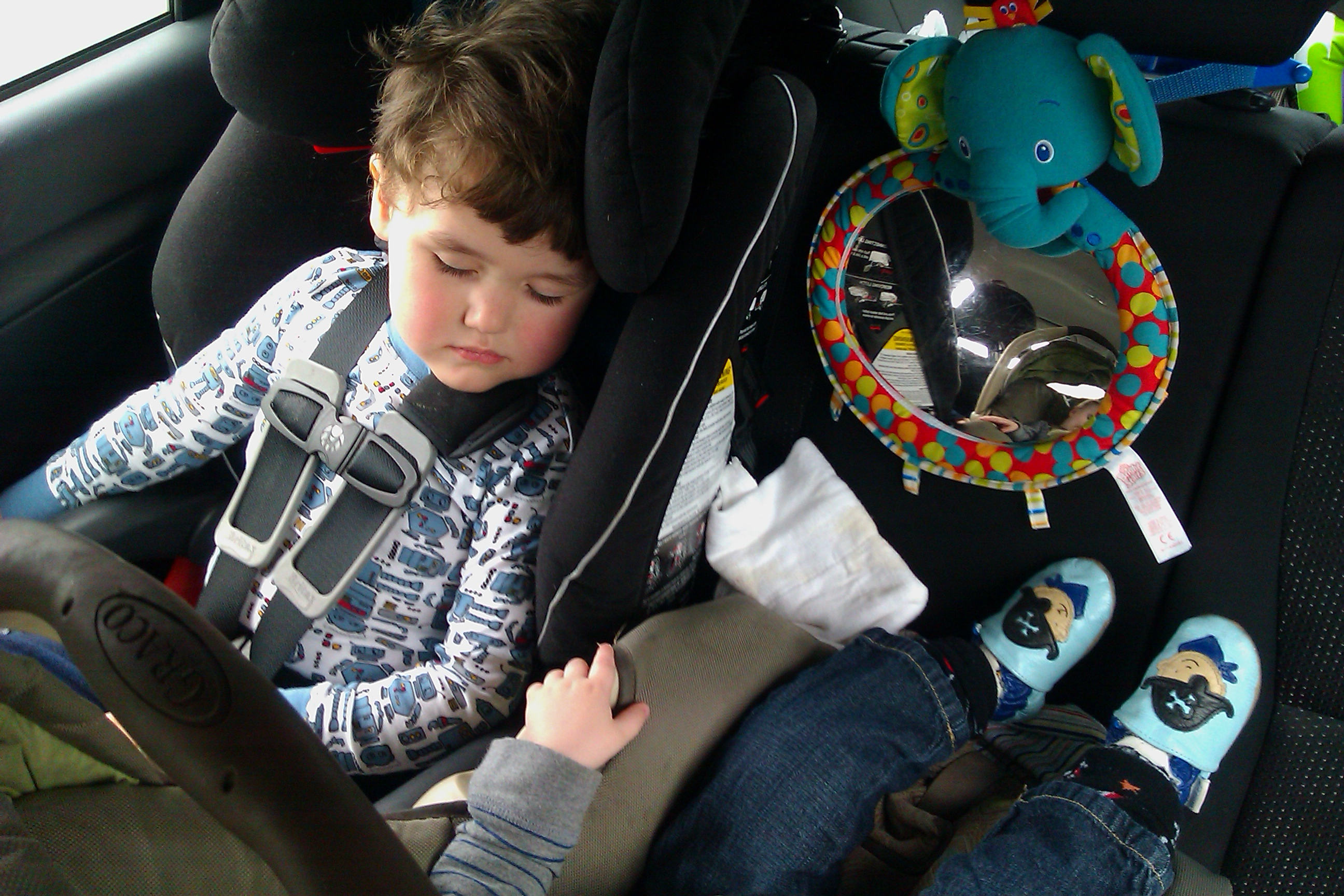 two kids asleep in car seats in the back