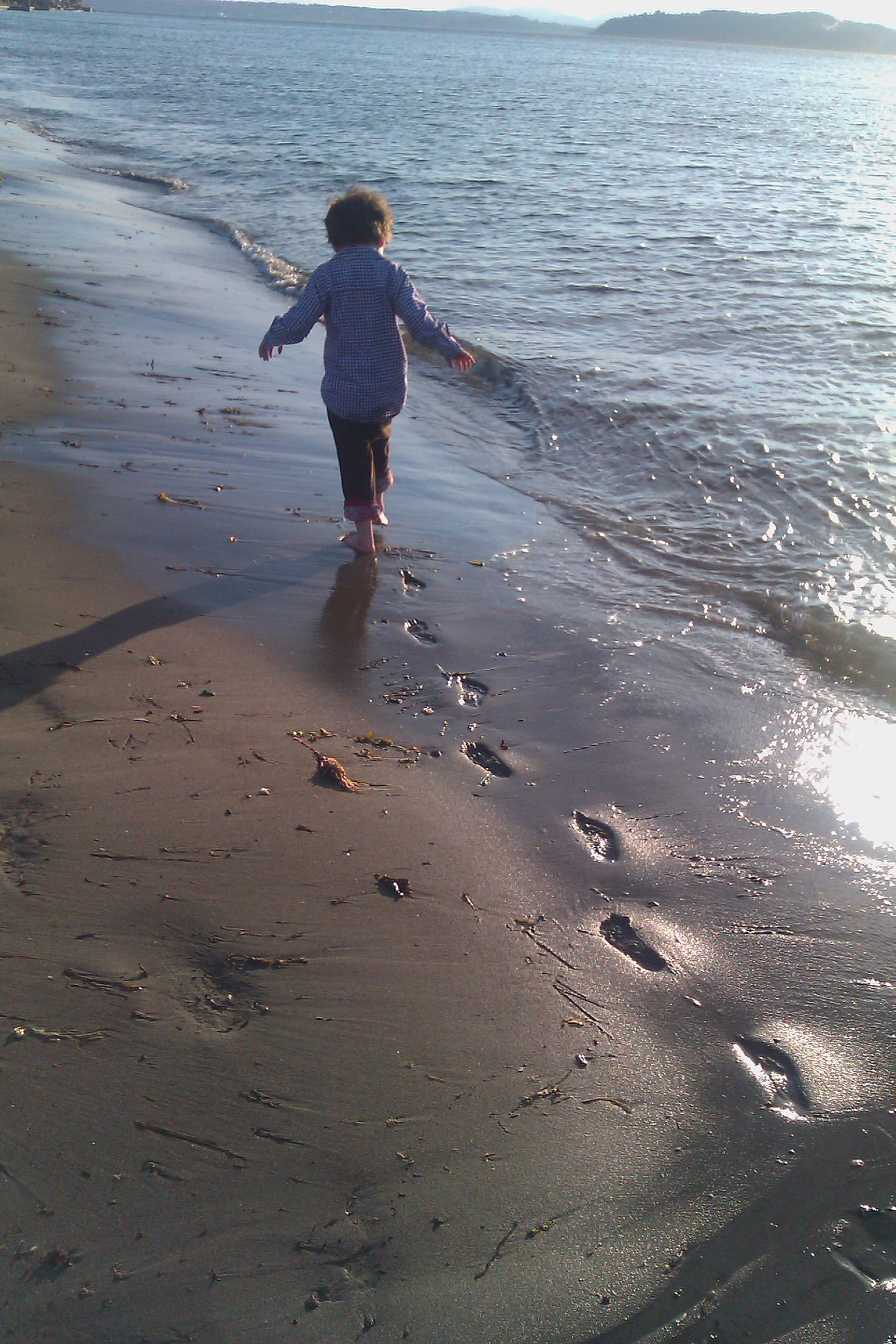 boy running along wet sand on beach