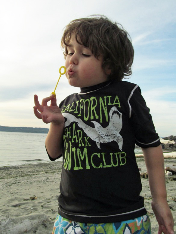 boy blowing bubbles on beach at family camping