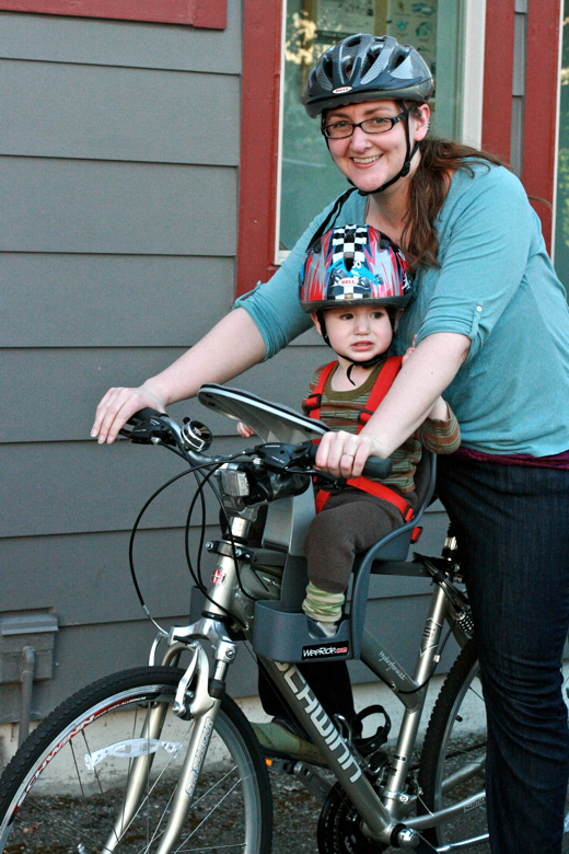 mom and toddler boy in bike helmets on bike with weeride seat - biking outdoors