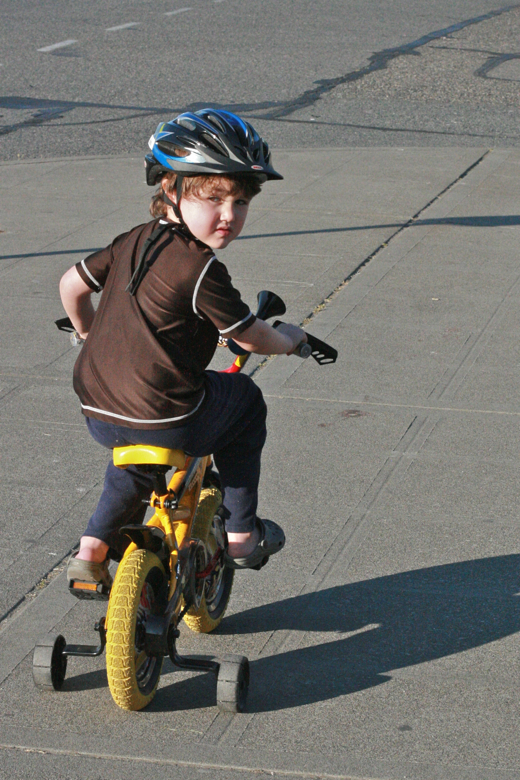 boy riding bike in helmet with training wheels - mikko m5yo biking outdoors