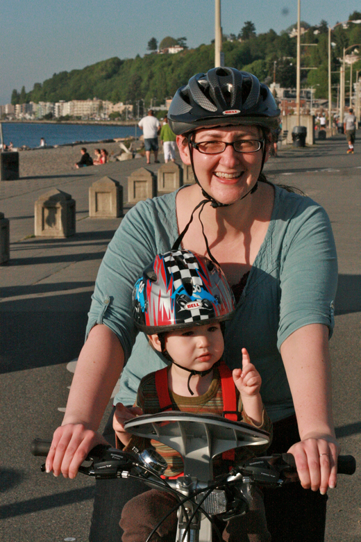 mom and toddler boy in bike helmets on bike with weeride seat on beach - biking outdoors
