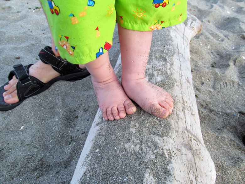 baby feet balancing on log on beach with mama in family camping