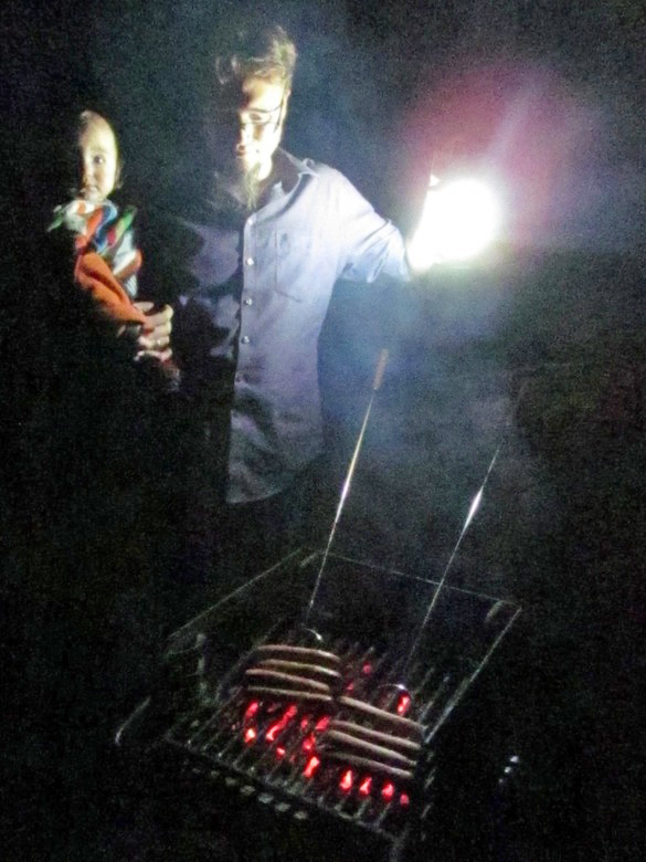 roasting hot dogs and marshmallows on grill in the dark in family camping