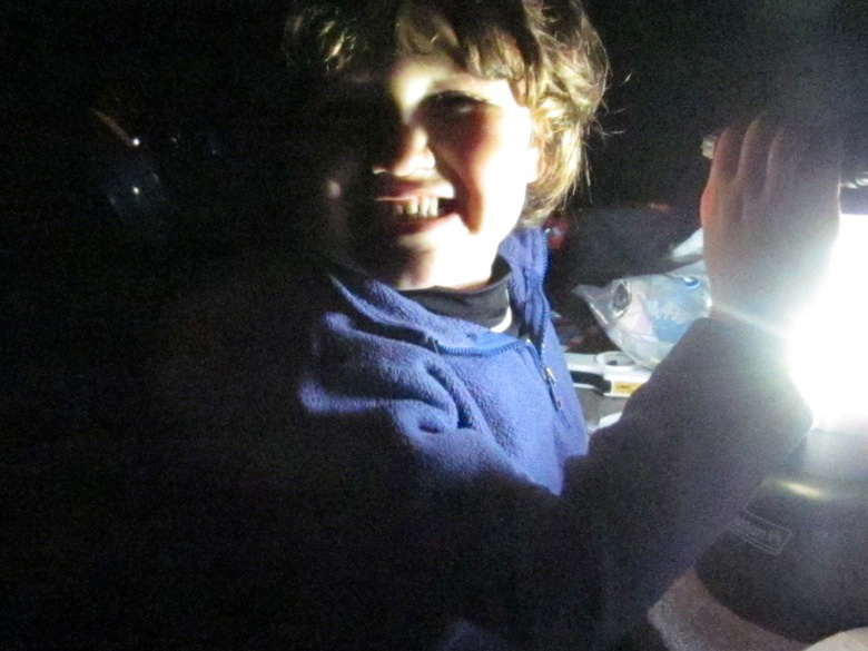 boy smiling in lantern light during dinner in family camping
