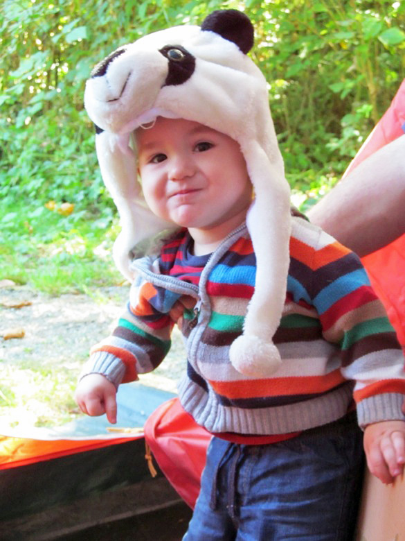 baby in panda hat in tent in family camping