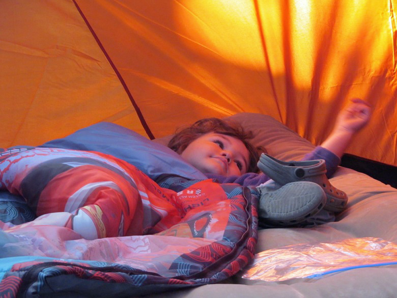 boy lying down in sleeping bag in tent in family camping