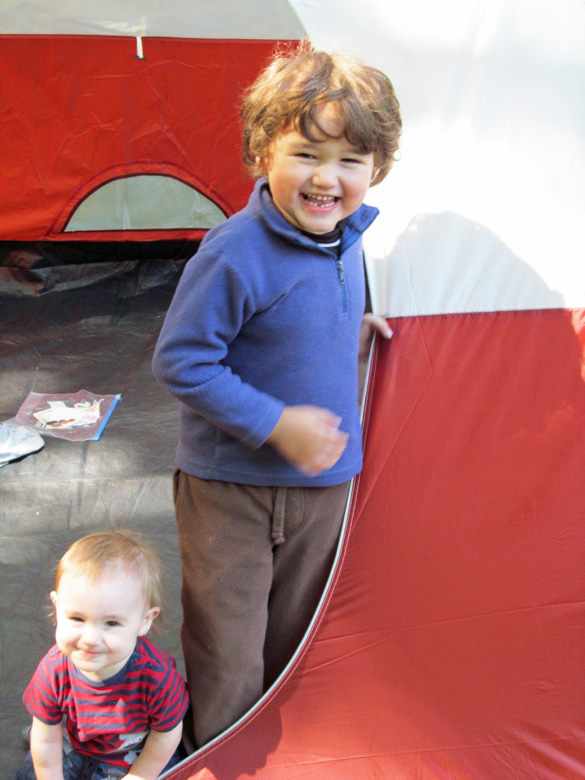 boys smiling in tent opening in family camping