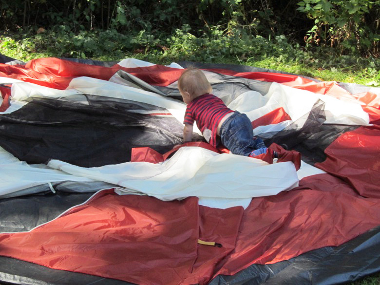 baby crawling on top of collapsed tent in family camping
