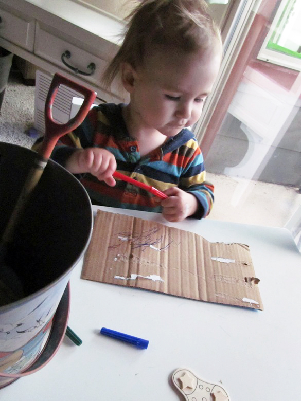 baby decorating cardboard with markers — holidays Christmas12