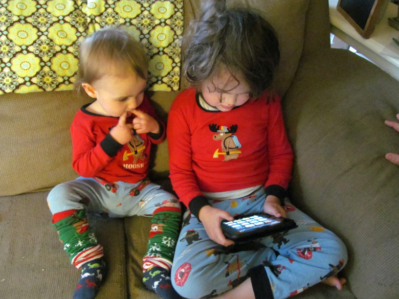 boys on couch on christmas morning opening kindle angry birds app —