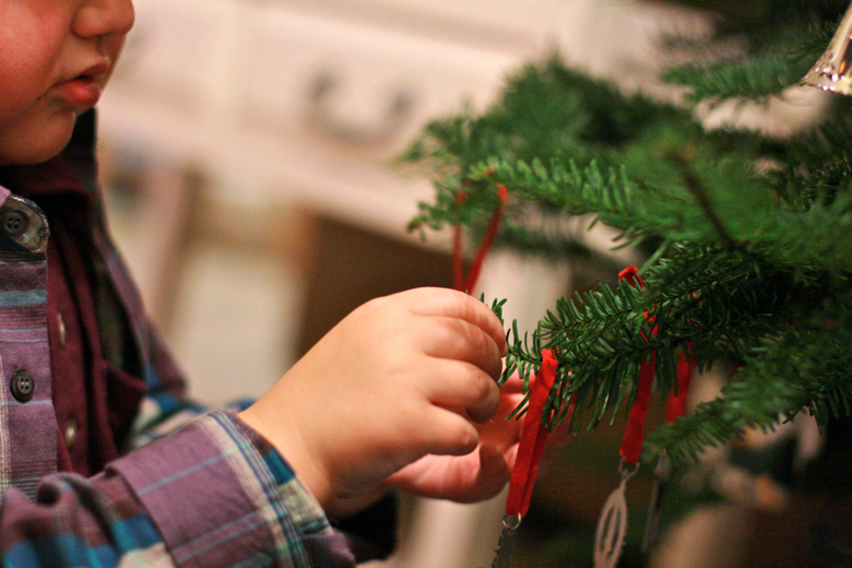 boy adding ornament on tree — Christmas 2011