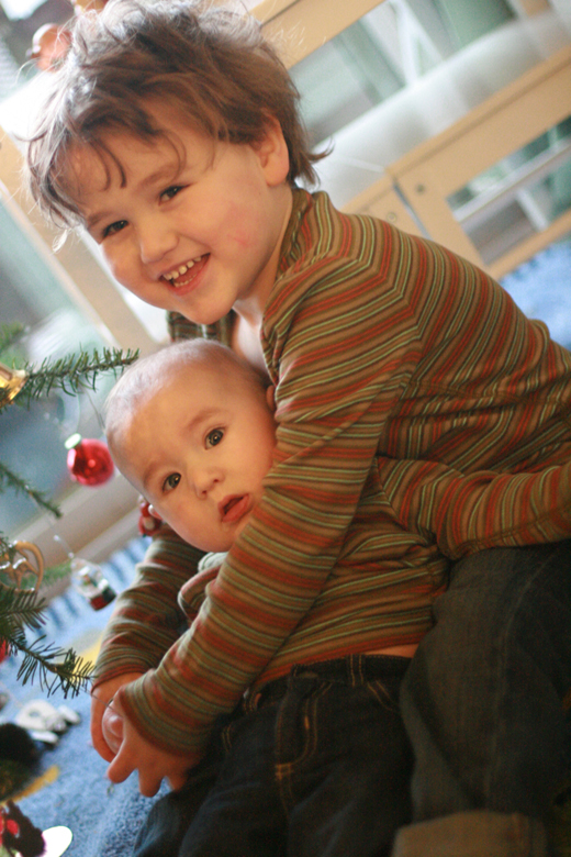 baby and boy at Christmas tree