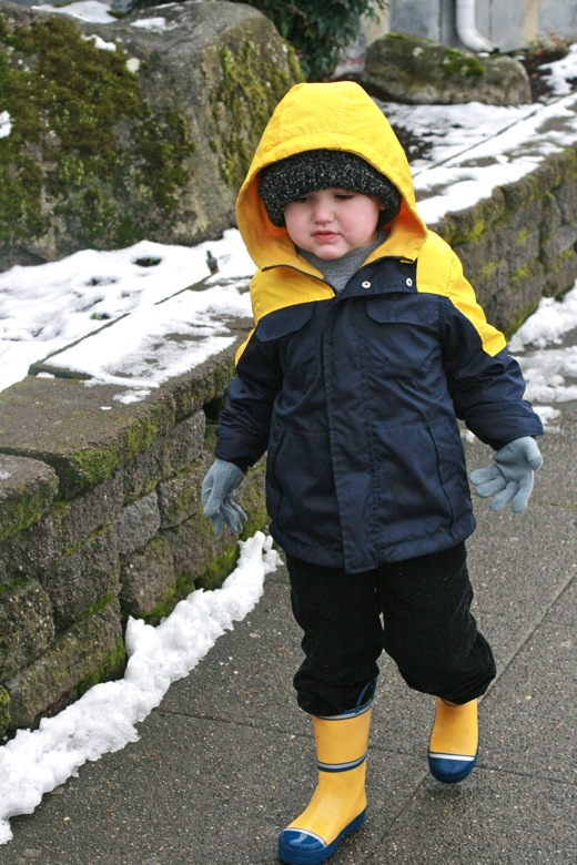 boy walking in snow jacket and boots in winter outdoors in Seattle