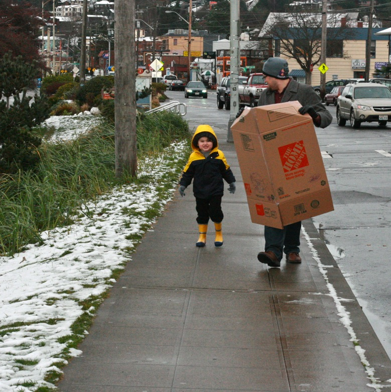 dad and boy carrying cardboard box sled in winter outdoors in Seattle